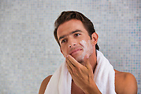 Portrait of attractive man cleansing his face with facial foam in the bathroom
