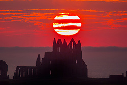 **Date correction*<br /> © Licensed to London News Pictures. 26/06/2018. Whitby UK. The sun sets last night (26/06/2018) behind the gothic ruins of Whitby Abbey on the Yorkshire coast as the uk looks forward to another hot day. Photo credit: Andrew McCaren/LNP