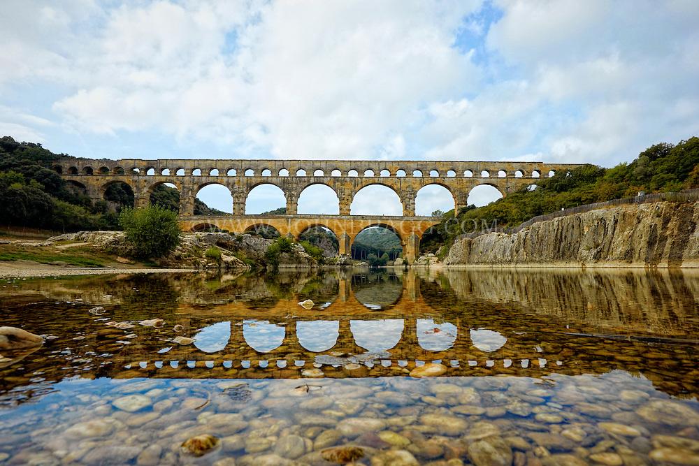 View of Pont du Gard (Roman Aqueduct), taken from the reflective waters of the Gardon River, Vers-Pont-du-Gard, France.
