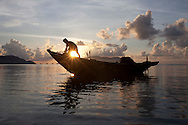 Fisherman on a boat moored along a shore in Con Dao island, Vietnam, Southeast Asia