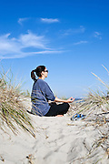 Woman practicing yoga at the beach, Cape Cod.