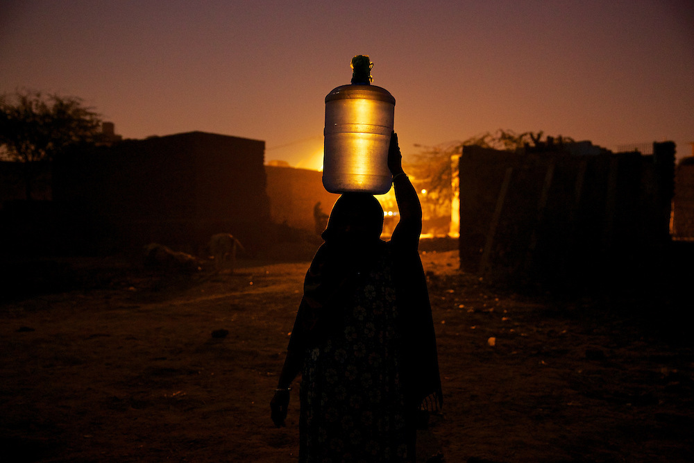 Silhouette of a woman carrying water bottle on head, India. Every day hundreds of millions of people wake up at dawn and work hard until sunset to find their way out of poverty. Many of these people cannot access clean water and electricity, nor pay school fees for their children or see a doctor when they are sick. Their basic needs have been largely unmet, neither by public services nor by the market that doesn't consider them as potential customers. Access to health care services in India by low-income people is limited due to the poor supply from the public service, especially in remote areas such as slums.