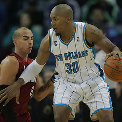 Dec 30, 2009; New Orleans, LA, USA;  New Orleans Hornets forward David West (30) is defended by Miami Heat guard Carlos Arroyo (8) during the first half at the New Orleans Arena. The Hornets defeated the Heat 95-91. Mandatory Credit: Derick E. Hingle-US PRESSWIRE