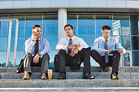 Mature businessmen sitting on stairs against office building after work
