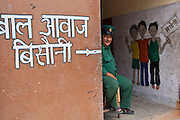 A Nepalese male security guard sits at the entrance of the Voice of Children rehabilitation center in Kathmandu, Nepal.  Nepalese writing on the wall directs visitors to the entrance.  On the other wall is a painted picture of 3 children.  The center supports street children and those who are at risk of sexual abuse through educational and vocational training opportunities, health services and psychosocial counseling.