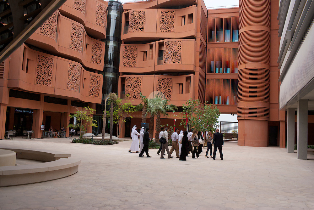 Masdar City. ASIEN, VEREINIGTE ARABISCHE EMIRATE, EMIRAT ABU DHABI, ABU DHABI, 14.04.2011: Besucher auf dem Campus des Masdar Instituetes. Die Wu?stenstadt Masdar sollte das Silicon Valley fu?r nachhaltige Technologien werden. 2006 rief Scheich Mohammad Bin Zayed al-Nahyan, Kronprinz von Abu Dhabi, das Projekt ins Leben. Die Fertigstellung des Projekts wird sich verzoegern: statt wie geplant 2016 wird die Oekostadt fruehestens 2025 fertig. - Stichworte: