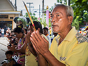 "23 JUNE 2015 - MAHACHAI, SAMUT SAKHON, THAILAND: People pray as the City Pillar Shrine is carried through town in Mahachai. The Chaopho Lak Mueang Procession (City Pillar Shrine Procession) is a religious festival that takes place in June in front of city hall in Mahachai. The ""Chaopho Lak Mueang"" is  placed on a fishing boat and taken across the Tha Chin River from Talat Maha Chai to Tha Chalom in the area of Wat Suwannaram and then paraded through the community before returning to the temple in Mahachai.   PHOTO BY JACK KURTZ"