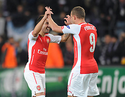 Arsenal's Santi Cazorla jokes with Arsenal's Lukas Podolski at the end of the game  - Photo mandatory by-line: Dougie Allward/JMP - Mobile: 07966 386802 - 22/10/2014 - SPORT - Football - Anderlecht - Constant Vanden Stockstadion - R.S.C. Anderlecht v Arsenal - UEFA Champions League - Group D