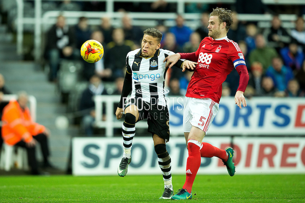 Newcastle United forward Dwight Gayle (#9) holds off Nottingham Forest defender Matthew Mills (#5) to unleash a shot during the EFL Sky Bet Championship match between Newcastle United and Nottingham Forest at St. James's Park, Newcastle, England on 30 December 2016. Photo by Craig Doyle.