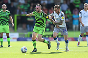 Forest Green Rovers Carl Winchester(7) fends off a challenge from Colchester United's Ben Stevenson(24) during the EFL Sky Bet League 2 match between Forest Green Rovers and Colchester United at the New Lawn, Forest Green, United Kingdom on 14 September 2019.