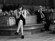 Young woman and older man using cellphones in a mini park near Madison Avenue in Midtown New York City.
