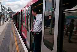 © Licensed to London News Pictures. 23/08/2012, London, UK.  A member of staff looks out from a DLR train at Poplar station in east London, Thursday, Aug. 23, 2012. DLR, Docklands Light Railway, is celebrates its 25th annivesary today. Photo credit : Sang Tan/LNP