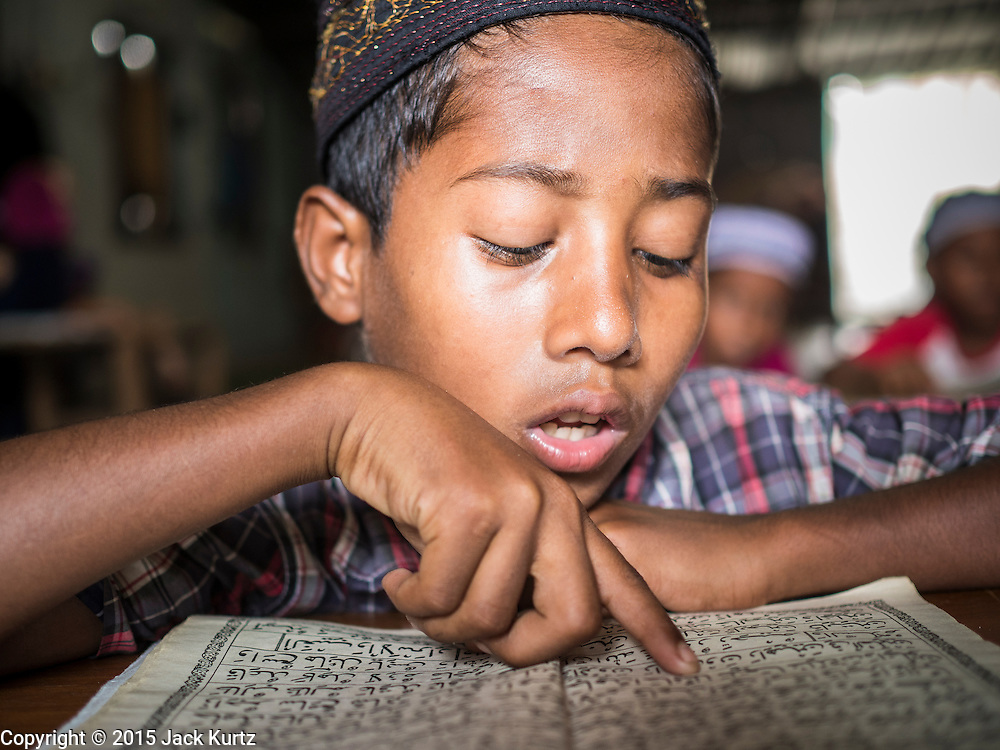 01 JUNE 2015 - KULAI, JOHORE, MALAYSIA:  A Rohingya boy recites the Koran in a madrasa (Muslim religious school) in Kulai, Malaysia. The Rohingya children are not allowed to attend Malaysian schools. Their madrasa is in a dilapidated building with holes in the roof and exposed wiring. The UN says the Rohingya, a Muslim minority in western Myanmar, are the most persecuted ethnic minority in the world. The government of Myanmar insists the Rohingya are illegal immigrants from Bangladesh and has refused to grant them citizenship. Most of the Rohingya in Myanmar have been confined to Internal Displaced Persons camp in Rakhine state, bordering Bangladesh. Thousands of Rohingya have fled Myanmar and settled in Malaysia. Most fled on small fishing trawlers. There are about 1,500 Rohingya in the town of Kulai, in the Malaysian state of Johore. Only about 500 of them have been granted official refugee status by the UN High Commissioner for Refugees. The rest live under the radar, relying on gifts from their community and taking menial jobs to make ends meet. They face harassment from Malaysian police who, the Rohingya say, extort bribes from them.       PHOTO BY JACK KURTZ