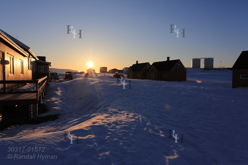 Late evening sun skims along horizon above the international science village of Ny-Alesund steeped in April snows on Spitsbergen island in Kongsfjorden; Svalbard, Norway.