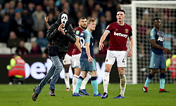 A pitch invader wearing a scream mask runs across the pitch during the Carabao Cup, Fourth Round match at the London Stadium.