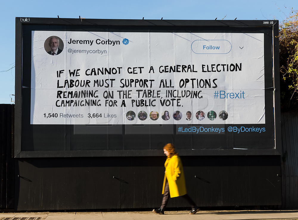 "© Licensed to London News Pictures. 14/02/2019. London, UK.  A woman walks past a new Jeremy Corbyn billboard from ""Led By Donkeys"" that has been put up in Mr Corbyn's Islington constituency with a message asking for Labour party support on a pubic vote on Brexit. A previous billboard, errected in the same place on Monday was reportedly removed by Islington Council, who later replaced the blank board when challenged. Photo credit: Vickie Flores/LNP"