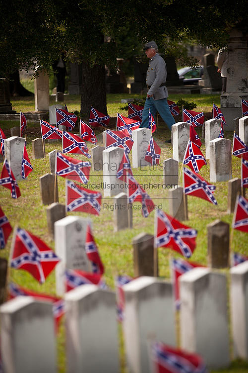 A Confederate re-enactor walks past Civil War battle flags on the graves of soldiers killed in the U.S. Civil War during Confederate Memorial Day May 10, 2011 in Charleston, South Carolina.  South Carolina is one of three states that marks the day as a public holiday.