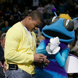 Mar 01, 2010; New Orleans, LA, USA; New Orleans Hornets mascot Hugo stands with New Orleans Saints running back Pierre Thomas in attendance courtside as he signs a football before throwing it to the crowd during the first half against the San Antonio Spurs at the New Orleans Arena. Mandatory Credit: Derick E. Hingle-US PRESSWIRE