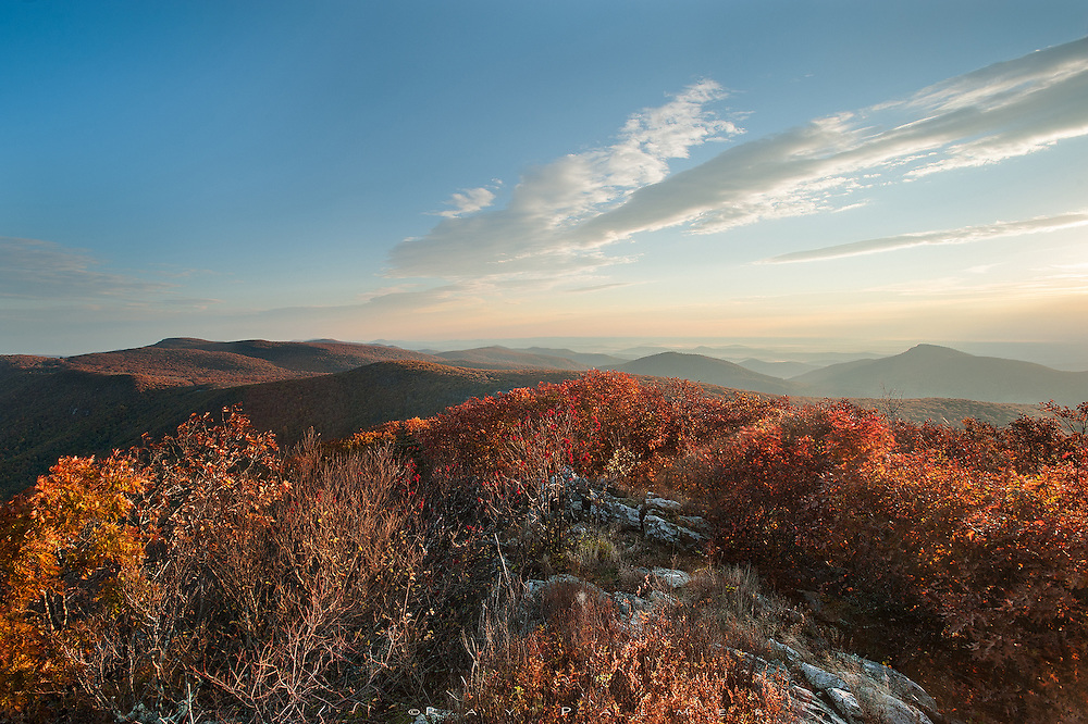 Shenandoah National Park, Virginia.<br /> <br /> I didn't want to get out of my sleeping bag.  It wasn't so much for lack of sleep as it was for the rude coldness on my exposed face.  But I hoped to catch sunrise from the highest point in Shenandoah, so I layered up, broke camp and drove to the trailhead with time to get to the top by sunup.  Great idea, but the eastern horizon was a stupid layer of haze and clouds, and sunrise nothing but an orange smudge behind it.  I waited, you never know.  Patience paid off after the sun cleared that layer and the light began raking across the Blue Ridge skyline arrayed northward before me.  The impressive bulk of Old Rag is viewed right, haze bound.