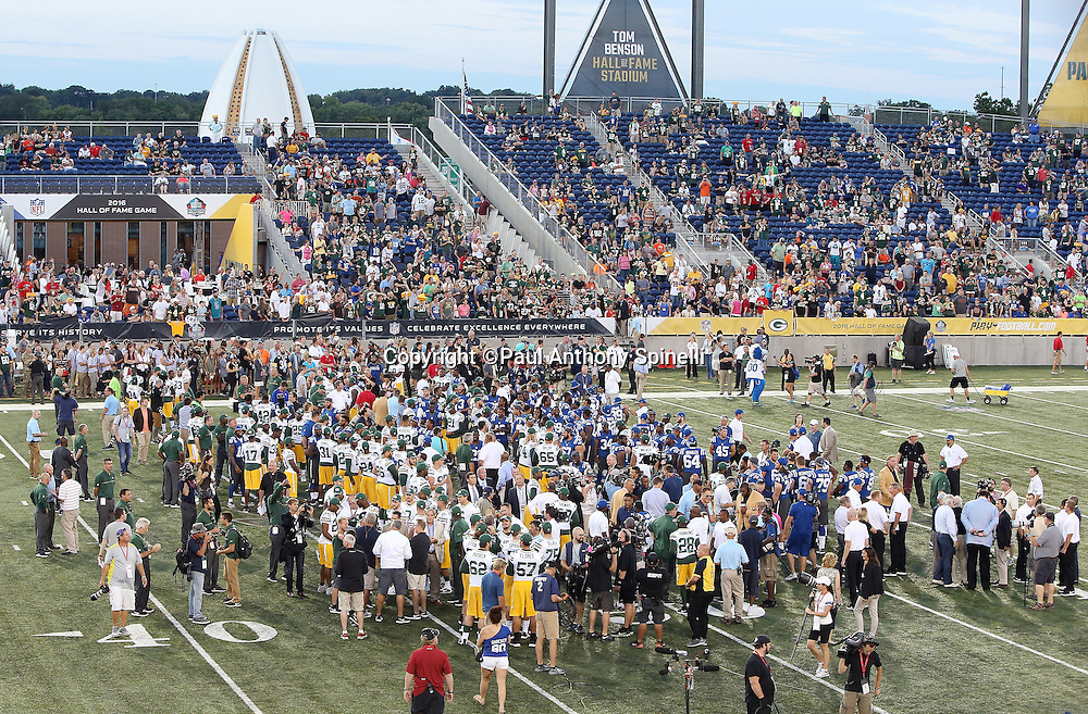 Memberss of the Indianapolis Colts and Green Bay Packers join members of the Pro Football Hall of Fame Class of 2016 during the public address announcement canceling the game before the 2016 NFL Pro Football Hall of Fame preseason football game between the Indianapolis Colts and the Green Bay Packers on Sunday, Aug. 7, 2016 in Canton, Ohio. The game was canceled for player safety reasons due to the condition of the paint on the turf field. (©Paul Anthony Spinelli)