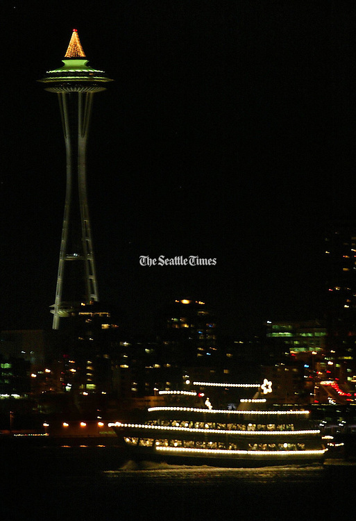 The lights of a Christmas ship illuminate the waters of Elliott Bay as it passes The Space Needle in the evening.<br /> Mark Harrison / The Seattle Times