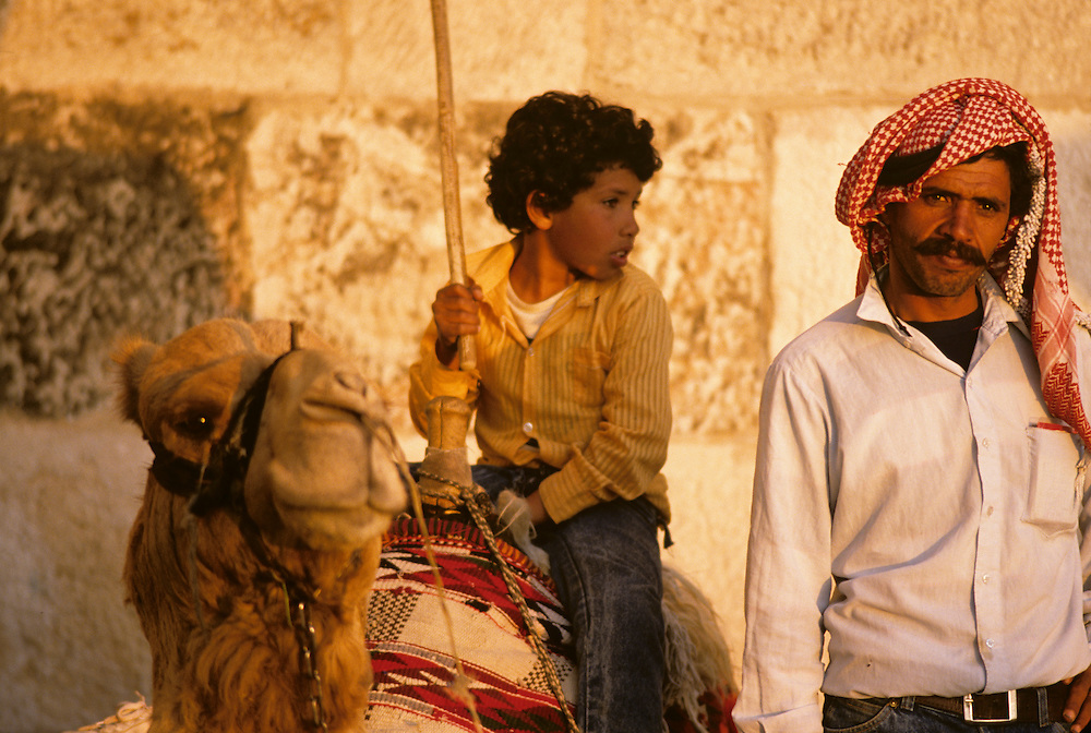 Israel, Jerusalem, Palestinian man wearing kaffiya offers camel rides outside walled city at sunset on spring evening