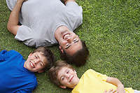 Father and two sons (6-11) lying on grass view from above