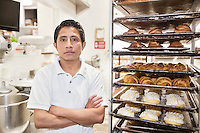 Portrait of young male baker with arms crossed in bakery