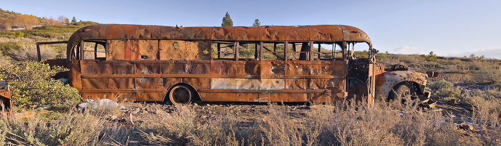 An image of an old school bus that has been shot full of holes near Truckee in California
