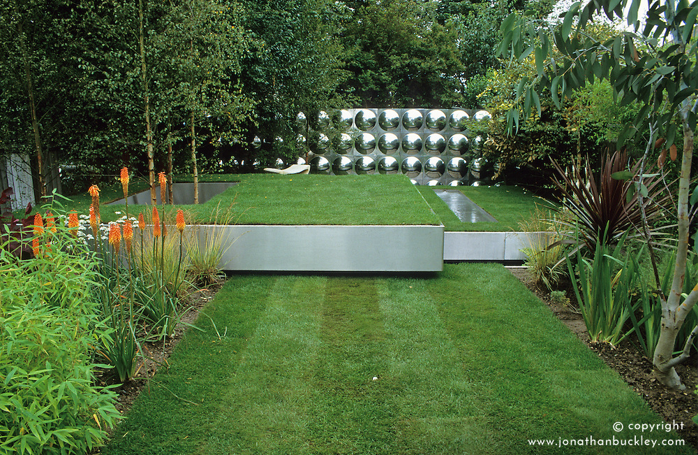 Three floating steel trays creating different levels of lawn. Workshop in distance clad with aluminium reflective disks. Design Diarmuid Gavin