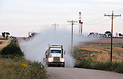 Fracking truck drives down a rural road with the Statoil drilling rig in the background.<br /> <br /> North Dakota oil boom. Based around the town of Williston, hydraulic fracturing, also known as 'fracking' has enabled a vast reserve of previously unobtainable oil to be accessed.