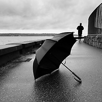 A running man during a rainy day, with an umbrella in the foreground.