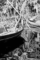 BANGLADESH BARISAL DISTRICT KURULIA SEP94 - A boy sits on his boat and leans on a pole stuck in the water...The Bangladesh Bureau of Statistics estimates the total working child population between 5 and 17 years old to be at 7.9 million...jre/Photo by Jiri Rezac..© Jiri Rezac 1994