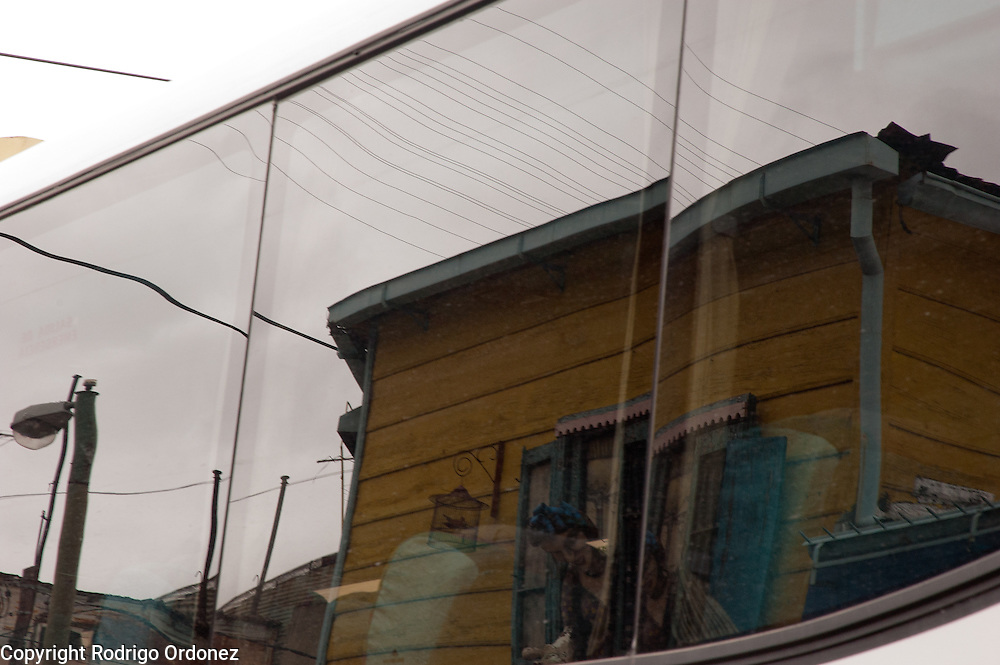 A bus window reflects the view of Caminito street, in La Boca neighborhood of Buenos Aires, Argentina.<br /> Caminito is a pedestrian street created in the late 1950s by local painter Benito Quinquela Mart&iacute;n and other artist friends to recreate a version of the old immigrant neighborhood of La Boca, using wood and corrugated zinc painted in bright colors. Today, Caminito and the surrounding areas feature cafes, souvenir shops, tango dancers and other street performances aimed to attract tourists.