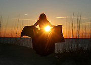 Nude woman opening cape to the warming sunrise rays on a Jekyll Island beach.