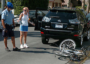 A parking enforcement officer pulled up behind a woman to give her a ticket, and ended up getting his bike crushed. The cop parked his bike behind the double parked motorist, and when he approached the side of her car, she backed over his bike. Photo taken in West Hollywood, CA 8-11-2007. (John McCoy/Staff Photographer)