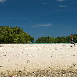 Papuan man walking across the white sandy beach.
