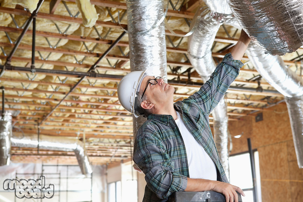 Construction worker working on unfinished ceiling