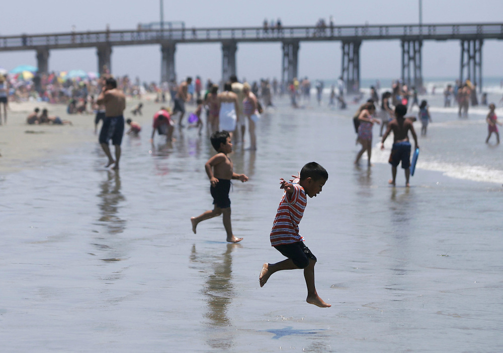 Children play near the pier in Newport Beach Saturday July 1, 2006.