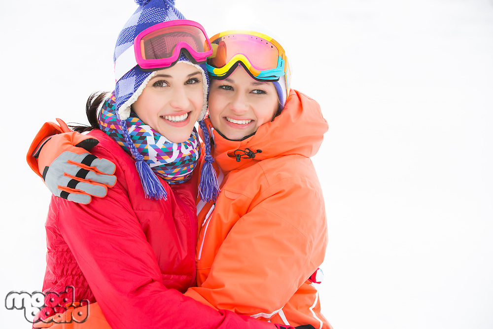 Portrait of happy young women in warm clothing embracing outdoors