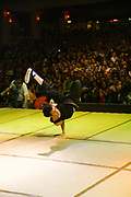 A dancer with glasses performing on stage in front of a big crowd of audience. UK B-Boy championships 06. 08/10/2006