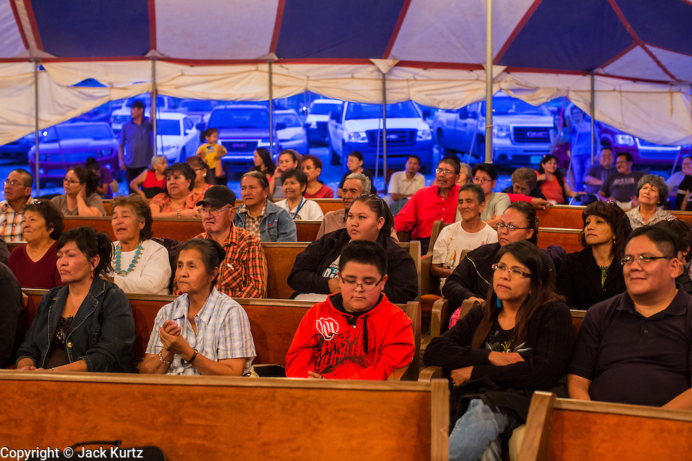 """12 JULY 2012 - FT DEFIANCE, AZ: At the 23rd annual Navajo Nation Camp Meeting in Ft. Defiance, north of Window Rock, AZ, on the Navajo reservation. Preachers from across the Navajo Nation, and the western US, come to Navajo Nation Camp Meeting to preach an evangelical form of Christianity. Evangelical Christians make up a growing part of the reservation - there are now more than a hundred camp meetings and tent revivals on the reservation every year. The camp meeting in Ft. Defiance draws nearly 200 people each night of its six day run. Many of the attendees convert to evangelical Christianity from traditional Navajo beliefs, Catholicism or Mormonism. """"Camp meetings"""" are a form of Protestant Christian religious services originating in Britain and once common in rural parts of the United States. People would travel a great distance to a particular site to camp out, listen to itinerant preachers, and pray. This suited the rural life, before cars and highways were common, because rural areas often lacked traditional churches.PHOTO BY JACK KURTZ"""