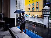17 NOVEMBER 2017 - YANGON, MYANMAR: A man under an umbrella walks through the rain in Yangon.      PHOTO BY JACK KURTZ