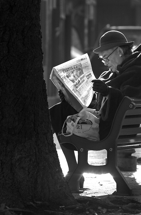 A woman reading newspaper on bench in Bologna Italy.
