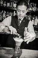 Bartender Shinobu Ishigaki is sprinkling gold flakes over his Matcha Martini at the Ishinohana Bar Shibuya,Tokyo, Japan
