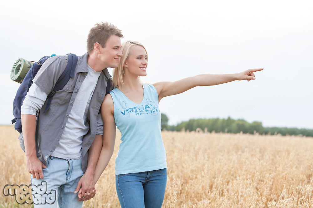 Happy female hiker showing something to man on field against clear sky