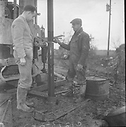 Lead Mines at Loughrea..1962..08.01.1962..01.08.1962..8th January 1962..Prospecting started in Loughrea in what is thought to be lead deposits beneath the lands of several small farms in the area...Image shows Mr Eamon O'Reilly one of the farmers involved watching the drill operator, Mr Tom Duffy, at work.