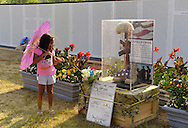 """East Meadow, New York, U.S. 11th September 2013. A young girl looks at the Battlefield Cross display in front of the Global War on Terror """"Wall of Remembrance"""" a traveling memorial on display in New York for the first time, at Eisenhower Park on the 12th Anniversary of the terrorist attacks of 9/11. The unique 94 feet long by 6 feet high wall has, on one side, almost 11,000 names of those lost on September 11th 2001, along with heroes and veterans who lost their lives defending freedom of Americans over past 30 years."""