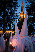 Hooded penitents (Nazarenos) in candlelit procession during Seville's annual Easter Holy Week (Semana Santa de Sevilla) one of the most important traditional events of the city. The annual celebrations mark the story of Christ's crucifixion and the Nazarenos walk through the historic Andalucian city in front of the devout in a series of processions. Several hundred members of the 57 religious brotherhoods (or Hermandades) from many of city churches accompany giant floats (Pasos) depicting the road to Calvary. The brotherhoods (founded in the mid 14th century) are associations of Catholic laypersons organised for the purpose of performing public acts of religious observance; in this case, related to the Passion and death of Jesus Christ and to perform public penance.