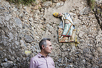 "PRAIANO, ITALY - 21 MAY 2016: Artist Enzo Caruso poses for a portrait next to one of her ceramic sculptures, in which he represents fantastic figures disguised as sirens, sailors or bishops with grotesque expressions., one of the eight art itineraries of the NaturArte project in Praiano, Italy, on May 21st 2016. Enzo Caruso's work revolves around the theme of the so-called janare, mythical figures often seen as witches. Through the janare, he intends to represent local folk mythology but also to make a reference to the many unconscious, dark fears people have.<br /> <br /> Over the previous three decades, Praiano had grown as part of the tourism boom of nearby Positano and the Amalfi Coast in general, but it had never developed its own identity or tried to shape its future. It is now trying to muscle in on the fame of better-known tourist drawn towns like Positano, Ravello and Amalfi, by positioning itself as an open-air museum. On Saturday, the town unveiled eight tourist itineraries, tracking the town's traditional small religious shrine made of majolica tiles, augmented with the works of eight contemporary artists.<br /> <br /> These shrines were built all over town to protect the Praianesi and their homes. The artists were asked to draw inspiration from the past or the local values and traditions and to revitalize and reinforce the concept of ""street art"" typical of the traditional shrines. The artists were also asked to create ceramic installations that would enhance and enrich the natural landscape. Their installations were not supposed to alter the nature and the local ""people's architecture"", but rather to enrich them in harmonious and elegant ways.<br /> <br /> The Praiano NaturArte Project consists of eight art itineraries. Seven of them have ceramic works (ceramic is a traditional medium in the area) and are made by some of the best and most well-known artists in the area."